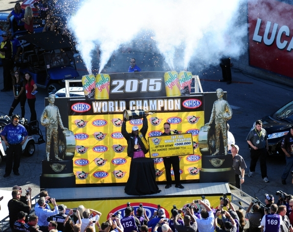 Top Fuel driver Antron Brown hoists the Mello Yello Top Fuel World Championship trophy after clinching it in the second round of the NHRA Top Fuel championship during eliminations for the Mello Ye ...