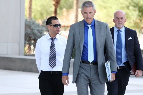 Ernesto Joshua Ramos, left, walks to Lloyd George Federal Courthouse in Las Vegas with his attorney Gabriel Grasso, center, to plead guilty to an extortion charge Tuesday, Nov. 3, 2015. Erik Verdu ...