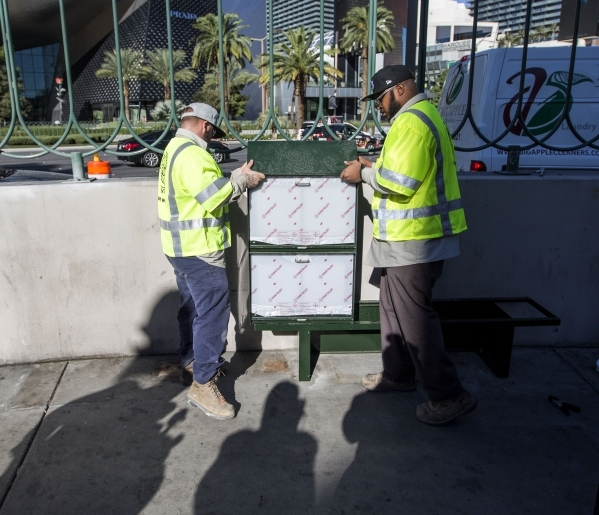 Clark County Public Works employees Edward Johnson,left, and Harold Hardwick  installs a new newsrack in front of Harley-Davidson Cafe, 3725 South  Las Vegas Boulevard, on Monday, Nov. 2, 2015. Th ...