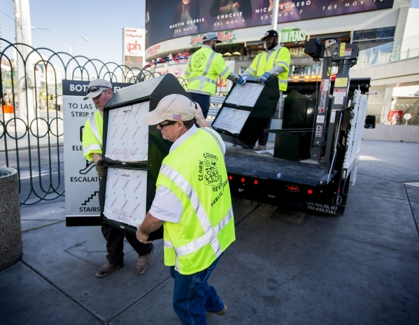 Clark County Public Works employees Kyle Buss, left, and Tyler Goodman carries a new newsrack in front of Harley-Davidson Cafe, 3725 South  Las Vegas Boulevard, on Monday, Nov. 2, 2015. The first  ...
