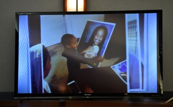 A video image is displayed of photograph of victim Kenny Cherry Jr. being held by one of his children during Ammar Harris's penalty hearing at the Regional Justice Center on Monday, Nov. 2,  ...