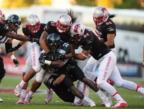 UNLV Rebels defensive linemen Sonny Sanitoa (93) and Jeremiah Valoaga (94) help tackle Hawaii running back Paul Harris (29) in the first half of their NCAA Football game at Sam Boyd Stadium in Hen ...