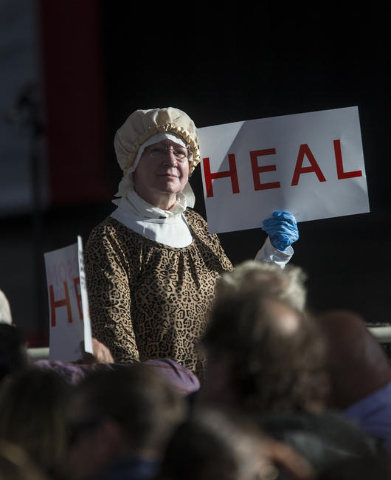 A lady in the audience holds a sign while waiting on retired neurosurgeon and Republican presidential candidate, Ben Carson to address the crowd, during a political rally at the Henderson Pavilion ...