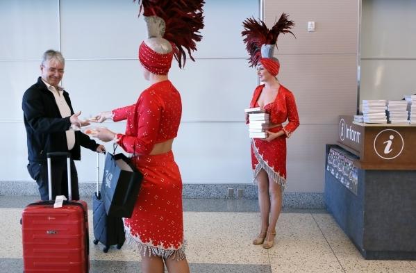 Norwegian Air passenger Benny Bredtaard (cq), left, of Denmark, is greeted by showgirls as he arrives from Copenhagen, Denmark, at McCarran International Airport Terminal 3 Tuesday, Nov. 10, 2015, ...