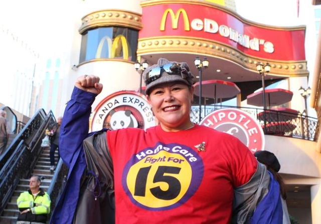 """Home care giver Teresa Sandoval shows off her t-shirt that reads """"Home Care Fight for 15"""" as she joined the local fast-food and child care workers protestesting outside a McDonald' ..."""