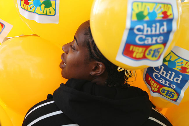 McDonalds employee Tia Williams holds balloons during a Fight For $15 rally in front of Las Vegas City Hall in Las Vegas Tuesday, Nov. 10, 2015. Fast food workers and supporters demand for a $15 h ...
