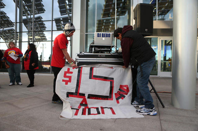 McDonald's employee Lee Throne, left, and community activist Martin Macias, put up a banner during a Fight For $15 rally in front of Las Vegas City Hall in Las Vegas Tuesday, Nov. 10, 2015.  ...