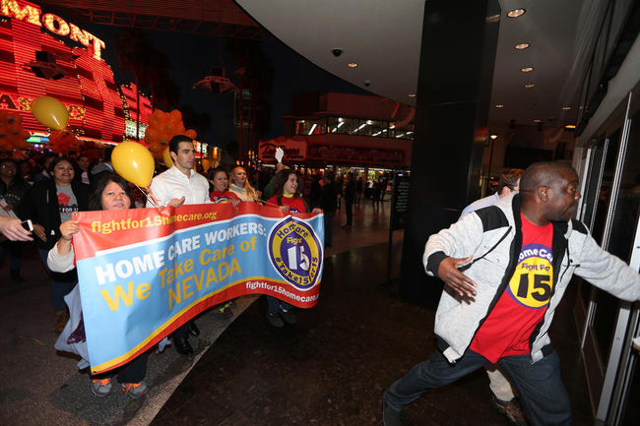 Demonstrators that included Nevada Sen. Ruben Kihuen, D-Las Vegas, second from left, march on Fremont Street to McDonald's inside The D Las Vegas casino-hotel for a Fight For $15 rally Tuesd ...
