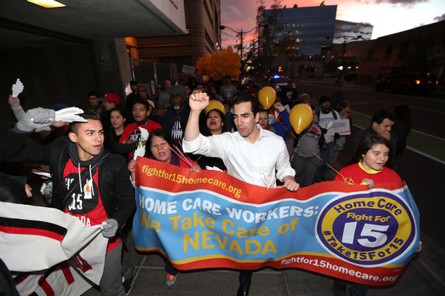 Carlos Martinez, from left, Dolores Rael, Nevada Sen. Ruben Kihuen, D-Las Vegas, and Teresa Martinez, 12, march to McDonald's on Fremont Street from Las Vegas City Hall during a Fight For $1 ...