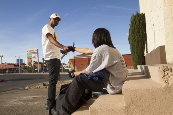 Vincent Pollard (left) , outreach manager at Nevada Partnership for Homeless Youth, provides a fast food restaurant gift card and shares information with a homeless teen about NPHY services to pro ...