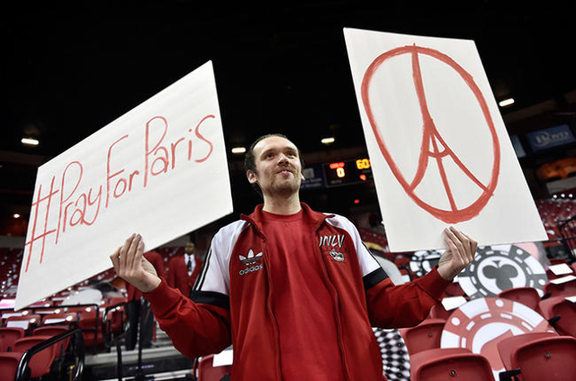Rebel fan Patrick Smith displays placards in support of Paris, France before a NCAA basketball game with Cal Poly visiting the UNLV Rebels at the Thomas & Mack Center in Las Vegas Friday, Nov. ...