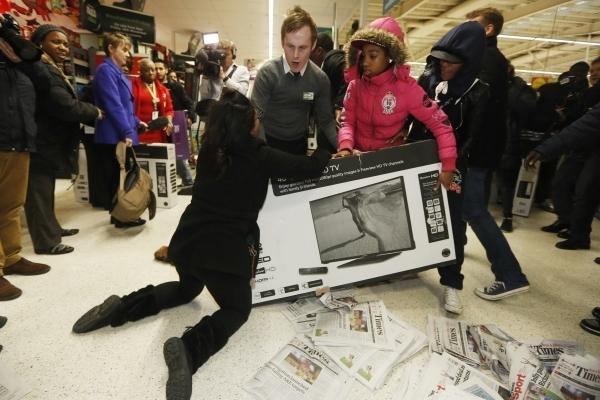 Shoppers wrestle over a television during a Black Friday sale last year in London. (Luke MacGregor/Reuters)
