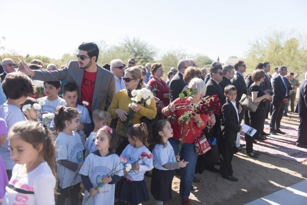 Children are given carnations to place on the monument's central bench during the unveiling and dedication of the Armenian Genocide Memorial Monument in Sunset Park in Las Vegas Saturday, No ...