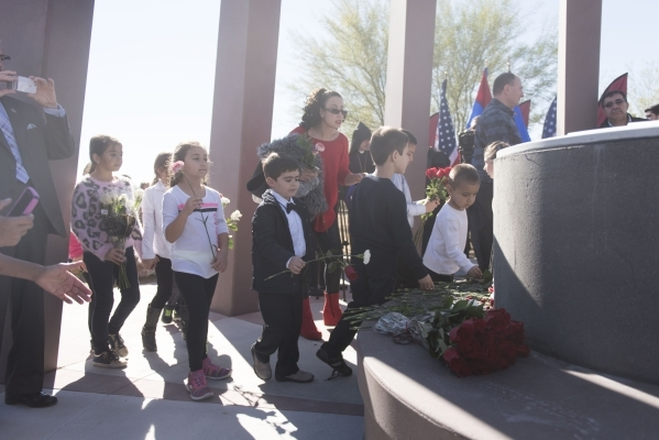 Children place carnations on the monument's central bench during the unveiling and dedication of the Armenian Genocide Memorial Monument in Sunset Park in Las Vegas Saturday, Nov. 14, 2015.  ...