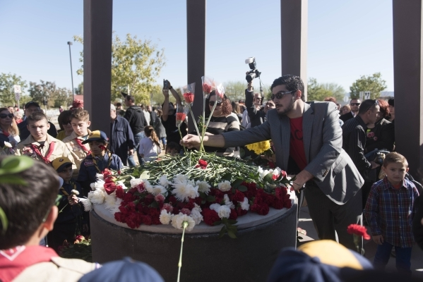 Vigen Khachikyan, chairman for the Armenian Church Youth Organization, right, organizes the carnations placed on the monument's central bench during the unveiling and dedication of the Armen ...