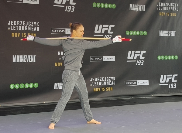 UFC women's bantamweight champion Ronda Rousey stretches Thursday at Federation Square in Melbourne, Australia, during open workouts for UFC 193 where she will defend the belt against Holly  ...