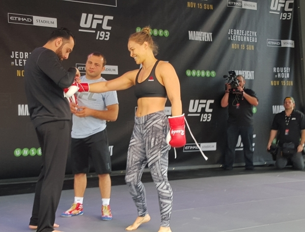 UFC women's bantamweight champion Ronda Rousey gets help with her gloves from coach Edmond Tarverdyan, left, Thursday at Federation Square in Melbourne, Australia, during open workouts for U ...