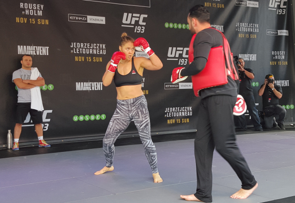 UFC women's bantamweight champion Ronda Rousey works out with coach Edmond Tarverdyan Thursday at Federation Square in Melbourne, Australia, during open workouts for UFC 193 where she will d ...