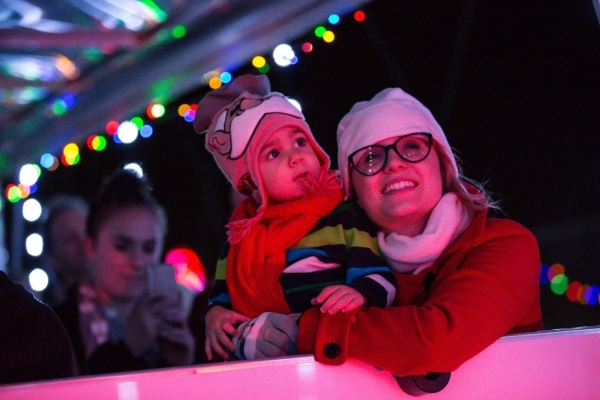 Two-year-old Gabriel Ochoa, with mother Paige, take in the sights during a ride on a trailer at the unveiling of Glittering Lights holiday drive-through light setup at Las Vegas Motor Speedway in  ...