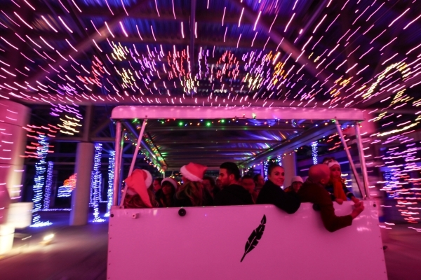 People Ride On A Trailer During The Unveiling Of Glittering Lights Holiday  Drive Through Light