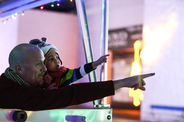 Two-year-old Gabriel Ochoa, with grandfather Dirk Hanson, take in the sights during a ride on a trailer at the unveiling of Glittering Lights holiday drive-through light setup at Las Vegas Motor S ...