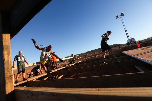Competitors balance on a wooden beam during the World's Toughest Mudder competition in Lake Las Vegas on Saturday, Nov. 14, 2015. Chase Stevens/Las Vegas Review-Journal Follow @csstevensphoto