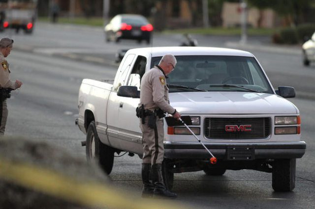 Police officers examine a pickup truck after a fatal accident involving a pedestrian on West Charleston Boulevard near Torrey Pines Avenue on Thursday, Nov. 12, 2015. (Brett Le Blanc/Las Vegas Rev ...