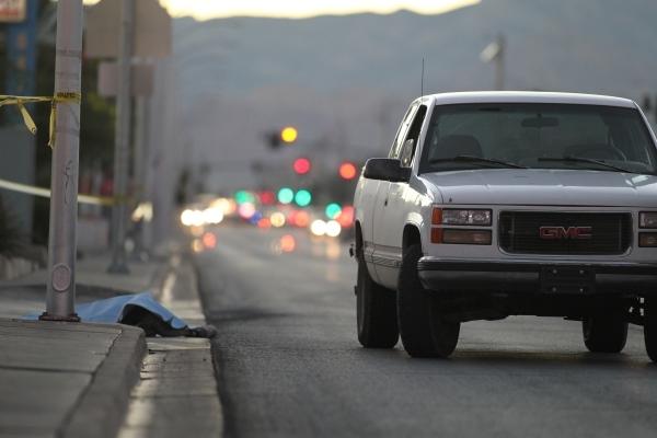 A sheet covers a body near the curb on West Charleston Boulevard near Torrey Pines following a fatal accident involving a pedestrian on Thursday, Nov. 12, 2015. Brett Le Blanc/Las Vegas Review-Journal