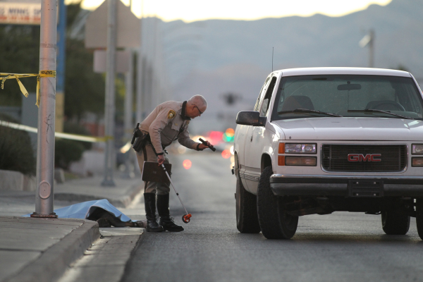 A police officer looks at a pickup truck on West Charleston Boulevard near Torrey Pines following a fatal accident involving a pedestrian on Thursday, Nov. 12, 2015. A sheet covers a body near the ...