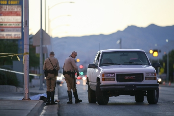 Police officers investigate a fatal accident involving a pedestrian on West Charleston Boulevard near Torrey Pines on Thursday, Nov. 12, 2015. A sheet covers a body near the curb behind the office ...