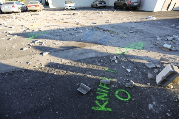 The scene of a fatal hit and run crash is seen on Thursday, Nov. 12, 2015, in Las Vegas. Police say the driver was assaulted by two men after an altercation. The attackers allegedly held onto the  ...