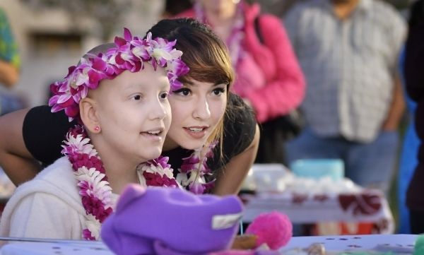 Natalia Ruiz, left, and her sister Elisa watch a performance by dancers from Hot Lava during a luau celebrating the announcement of NataliaþÄôs Make-A-Wish Foundation trip to Hawaii at Le ...
