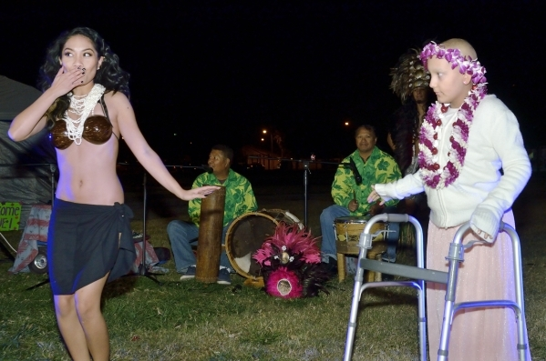 Hokulani Keali'inohomoku, left, demonstrates part of a hula for Natalia Ruiz during a luau celebrating the announcement of RuizþÄôs Make-A-Wish Foundation trip to Hawaii at Lewis Pa ...