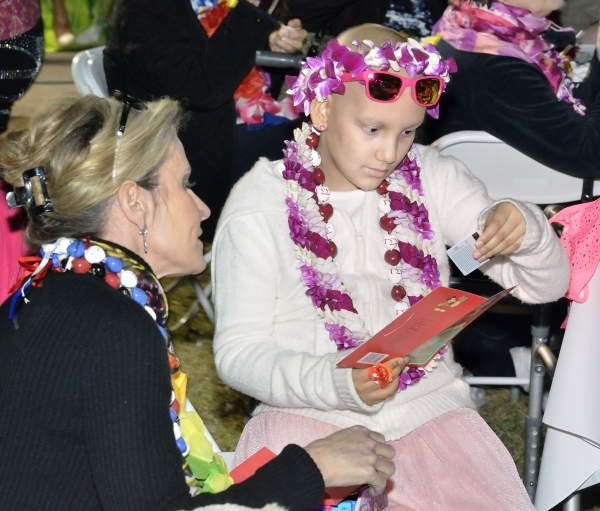 Wish granter Jackie Katz, left, looks on as Natalia Ruiz opens one of the gifts she received during a luau celebrating the announcement her Make-A-Wish Foundation trip to Hawaii at Lewis Park at 1 ...