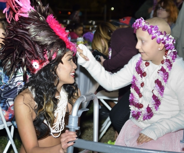Natalia Ruiz, right, checks out Hokulani Keali'inohomokuþÄôs headdress during a luau celebrating the announcement of RuizþÄôs Make-A-Wish Foundation trip to Hawaii at Lewis ...