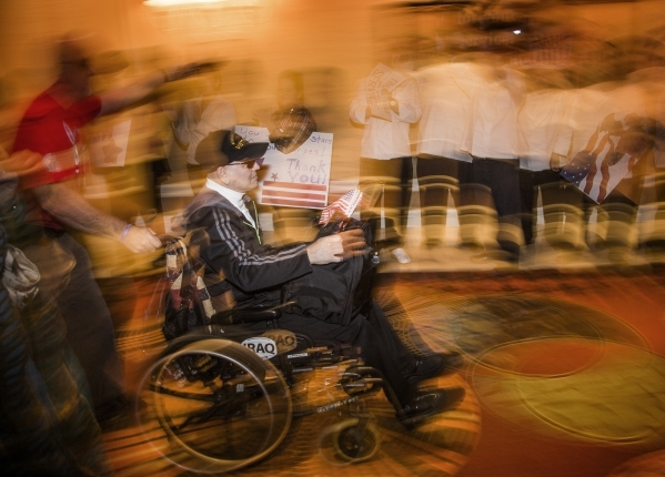 "Vietnam veteran Steve Bentancourt  waves a flag while MGM International employees cheer during the ""Salute the Troops"" event at the The Mirage on Friday, Nov. 13, 2015. MGM Resorts Inter ..."