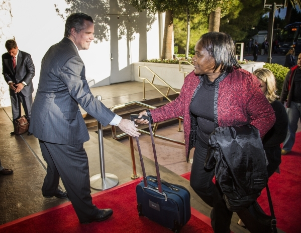 """Jim Murren, chairman and CEO of MGM Resorts International, helps a guest with her bag during the """"Salute the Troops"""" event at the The Mirage on Friday, Nov. 13, 2015. MGM Resorts Interna ..."""