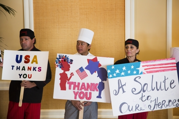 "Sergio Lopez, left, Emmanuel Almazan and Juliet Shahinian  holds signs during the ""Salute the Troops"" event at the The Mirage on Friday, Nov. 13, 2015.MGM Resorts International is treati ..."