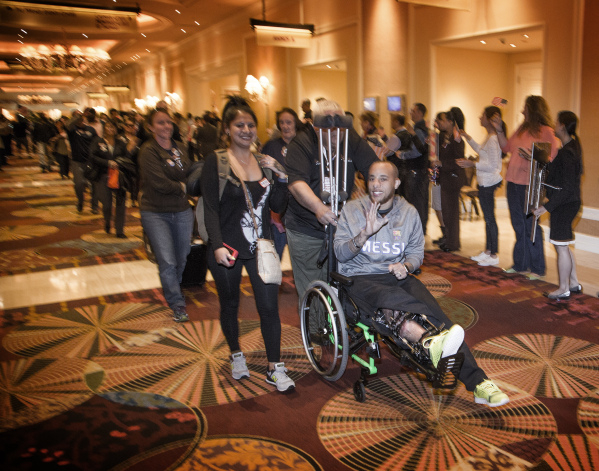 "Wound Warrior Allan Thomas waves to supporters while his wife Gabriella pushes his wheelchair during the ""Salute the Troops"" event at the The Mirage on Friday, Nov. 13, 2015. MGM Resorts ..."