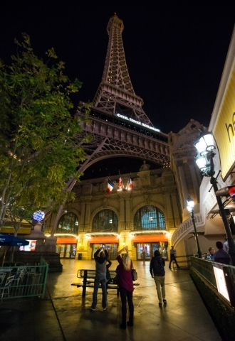 People take photos of a dimmed Eiffel Tower at the Paris hotel-casino in Las Vegas on Friday, Nov. 13, 2015. The tower was dimmed for the night following the attacks in Paris. Chase Stevens/Las Ve ...