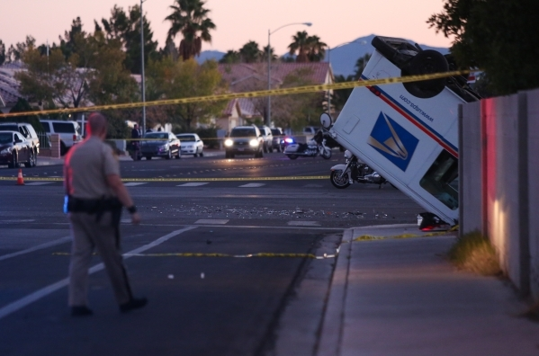 Las Vegas Police work the scene of a fatal wreck at the intersection of Mount Hood Road and Owens Avenue involving three cars, one of them a United States Postal Service mail truck on Saturday, No ...