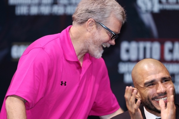 """Freddie Roach stands to speak as Miguel Cotto smiles during the final press conference for Saul """"Canelo"""" Alvarez and Cotto at Mandalay Bay casino-hotel in Las Vegas Wednesday, Nov. 18, 2 ..."""
