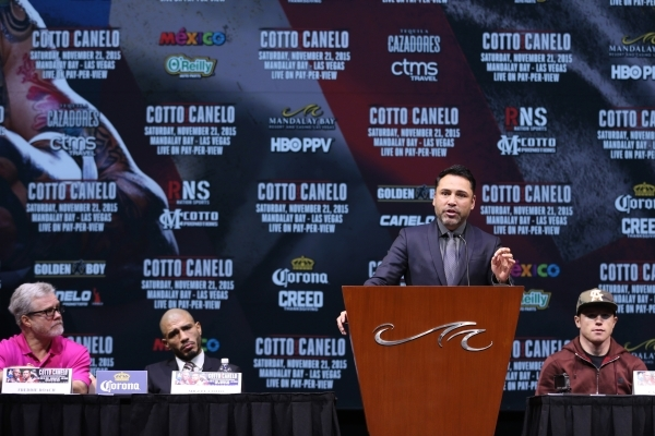 """Boxing promoter Oscar De La Hoya speaks at the podium as boxing trainer Freddie Roach, from left, Miguel Cotto and Saul """"Canelo"""" look on during the final press conference for the fight b ..."""