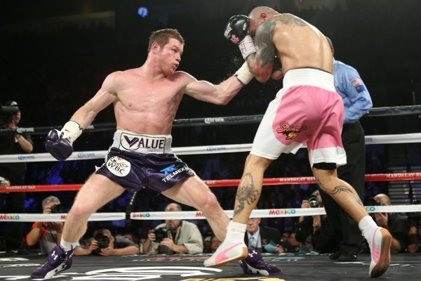"Saul ""Canelo"" Alvarez, left, throws a left punch against Miguel Cotto in their WBC middleweight title bout at the Mandalay Convention Center in Las Vegas Saturday, Nov. 21, 2015. Canelo  ..."