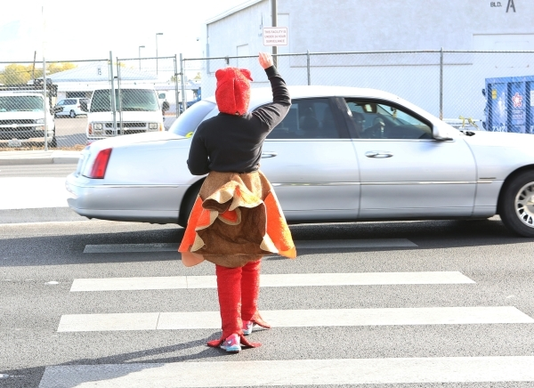 Trooper Chelsea Stuenkel dressed as a turkey crosses N. Eastern Avenue to see who fails to yield during pedestrian safety event on Wednesday, Nov. 18, 2015. The driver of the Lincoln Continental w ...