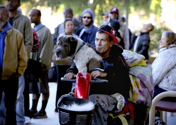 Jason Sellers sits on a electric scooter while his dog Freddie sits on his lap while waiting in line during Project Homeless Connect at Cashman Center at 850 N. Las Vegas Boulevard on Tuesday, Nov ...