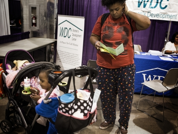 Tanisha Cross looks at brochure while looking for short term housing for her daughters DeVonee, left, three months, and Nahla, 2 1/2 years, during Project Homeless Connect  at  Cashman Center at 8 ...