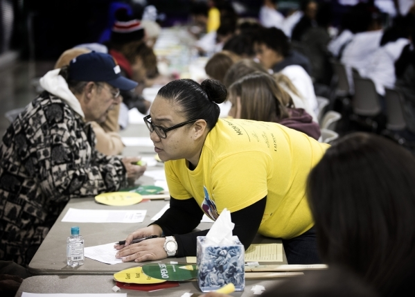 Volunteer Rica Lucio leans over a table to assist a client during Project Homeless Connect  at  Cashman Center at 850 N. Las Vegas Boulevard on Tuesday, Nov. 17, 2015. About 400 volunteers helped  ...