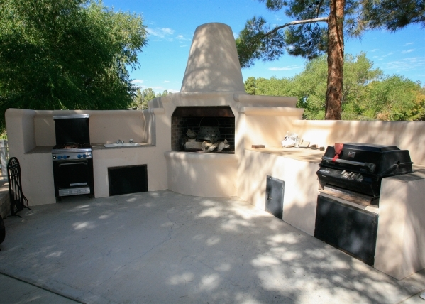"Outside the living room and kitchen, is a wide back patio with a barbecue area including an outdoor ""horno"" — or a conical fireplace. ELKE COTE/REAL ESTATE MILLIONS"
