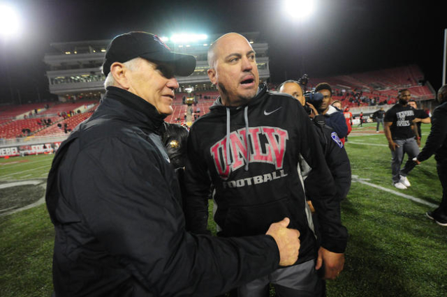 UNLV Rebels head coach Tony Sanchez, right, chats with San Diego Staten Aztecs head coach Rocky Long at the completion of their NCAA Football game against UNLV at Sam Boyd Stadium in Henderson Sat ...